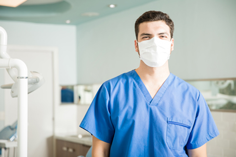 Woman in hospital scrubs and face mask