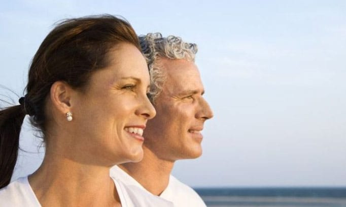 Photo of a middle-aged couple on a beach enjoying their great vision after LASIK or PRK
