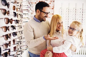 Family browsing glasses at optometry store